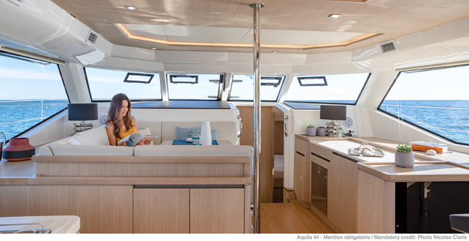 Woman relaxing in interior of Aquila 44 catamaran