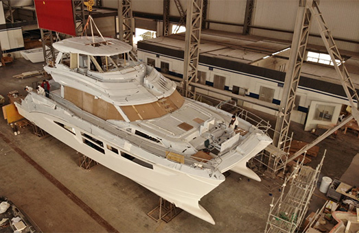 An Aquila power catamaran being constructed in a factory