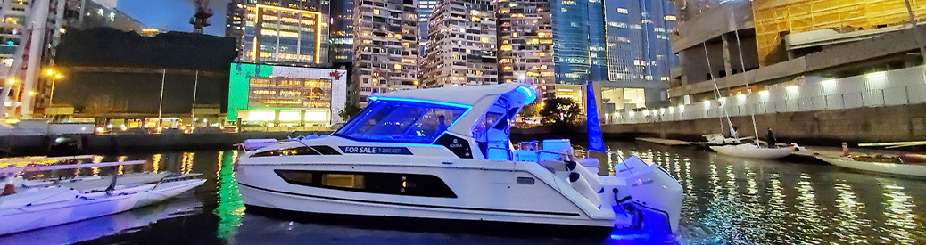 An Aquila power catamaran in the water at night