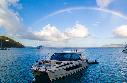 An Aquila 36 power catamaran in the blue water of the British Virgin Islands, with a rainbow overhead