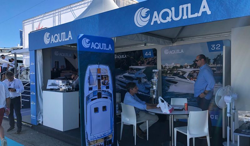 the aquila booth at the cannes yachting festival with people walking in and out of the blue tent