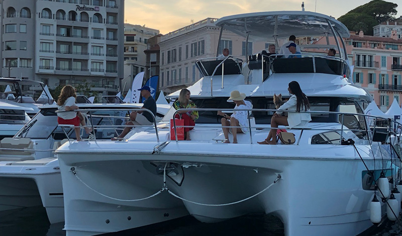 people seated on the bow and flybridge of the aquila power catamaran while docked in cannes france at dusk