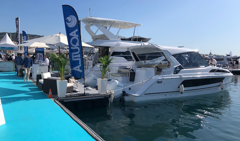 aquila power catamarans docked at the cannes yachting festival with an aquila banner waving