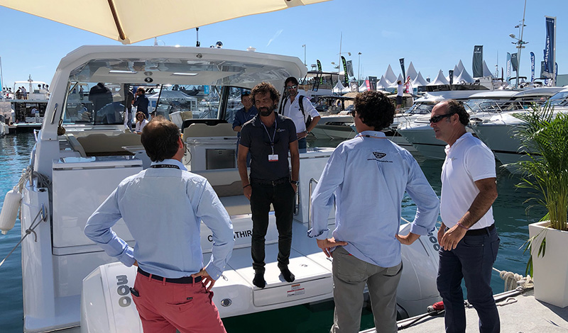 a man standing on the stern of an aquila power catamaran and having a conversation with three men standing on a dock