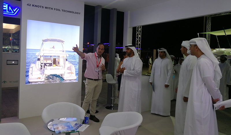 a group of men in the aquila booth at a boat show with a photo of an aquila power catamaran on the wall next to them