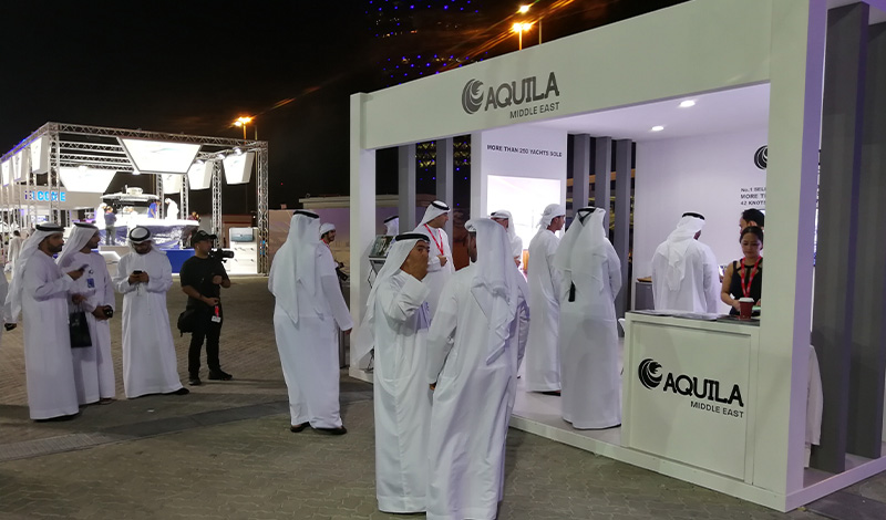 people standing outside of an aquila booth at the abu dhabi international boat show at night