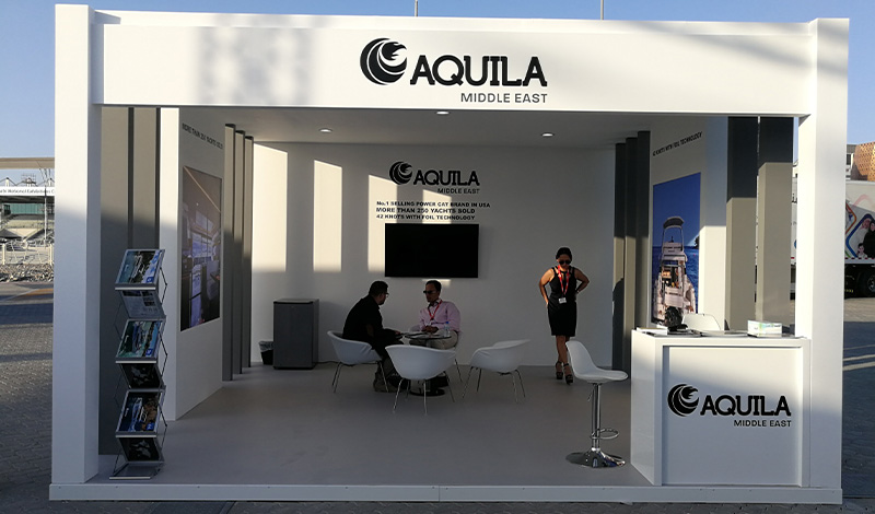 three men seated around a table at a boat show in front of a sign saying aquila