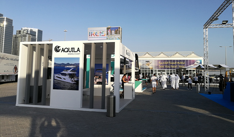 a white aquila booth at the abu dhabi international boat show