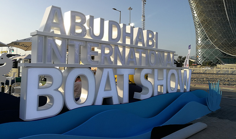 a sign of white letters saying abu dhabi international boat show