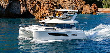 Aquila 44 cruising through the Mediterranean with couple on flybridge