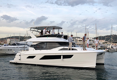An Aquila power catamaran anchored in a marina in Cannes France with several people aboard