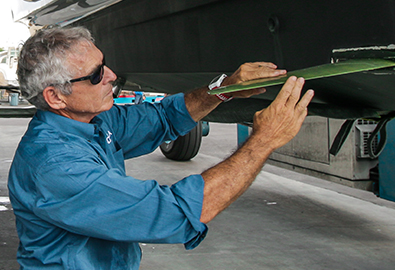 A man in a blue shirt holding a piece of metal up to the hull of a boat in a warehouse