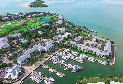 Aerial view of Captiva Island, with docked boats at the marina, a golf course in the background, and beautiful blue water around it