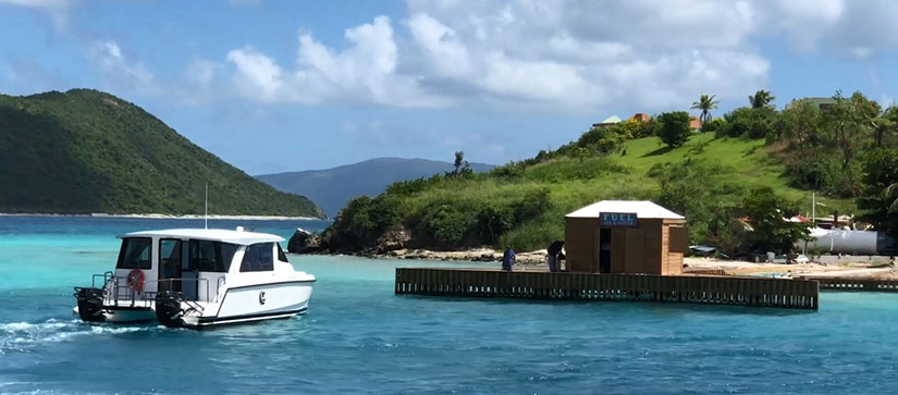 An Aquila 36 Excursion cruising towards a fuel station in the British Virgin Islands, surrounded by blue water