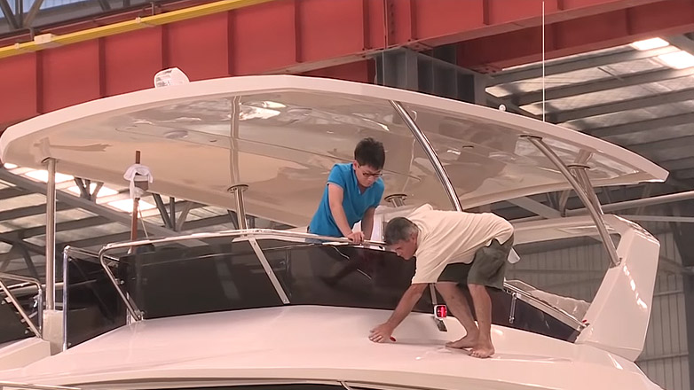 Two people working on Aquila boat in factory